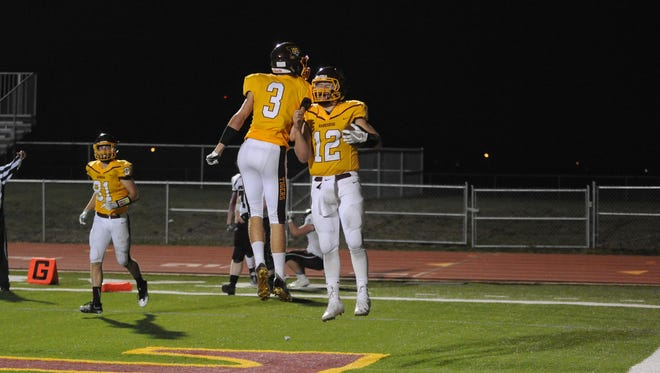 Harrisburg quarterback Hunter Headlee (12) celebrates with Justis Clayton after Headlee scored in the semifinal game Friday night at Harrisburg. The Tigers won 61-7.