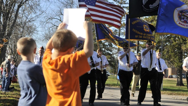 Landon Phillipp and Brayden West hold signs for passing veterans during the annual Veterans Day Parade