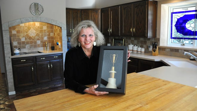 "Sharron Ann Sibley recently completed renovations of her parents'  house at 25 Augusta Drive, built in 1981. The late Sonoma and Dr. William ""Dub"" Sibley were one of the first to build a residence in Fairway Oaks. On Friday, Nov. 18, 2016, Sharron Ann holds a display box of a 1950 golf trophy her father won. Workers found it behind a garage wall. The butcher block table that is now part of the breakfast bar was originally built by William in 1952 for a previous family residence."