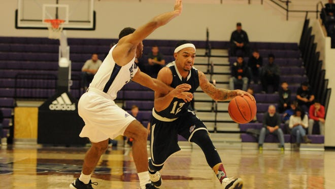 Justin Robinson's tries to drive past a defender Sunday afternoon during the first half of Monmouth University's 80-77 win over Holy Cross