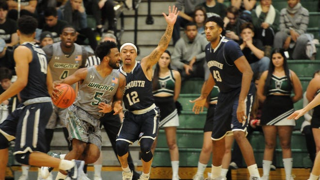 Monmouth University's Justin Robinson (12) defends JoJo Cooper during the first half of a game at Wagner College on Tuesday evening