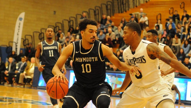 Monmouth University's Micah Seaborn makes a move to the basket as St. Peter's Trevis Wtche defends
