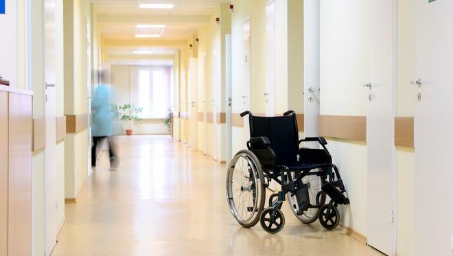 A wheelchair sits empty in a medical facility hallway.