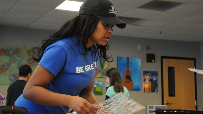 Chelsea Gans, program coordinator with the Boys and Girls Club of Salem, works with students on MLK Jr. Day, Monday, Jan. 16, 2017, to make posters honoring the historic civil rights leader.