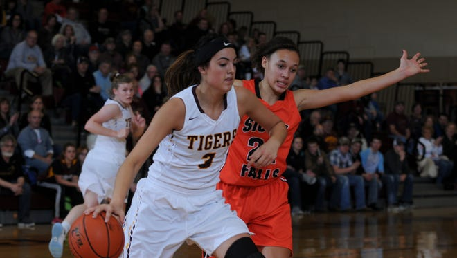 Harrisburg's Sam Slaughter (3) drives around Sioux Falls Washington's Jada Cunningham in varsity action Monday night in Harrisburg. The #1 ranked Tigers won 62-55.