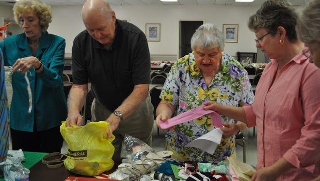 FILE IMAGE Happy Timers volunteers sort through material to be made into pillowcase dresses to prepare for a previous Happy Timers indoor yard sale. The group have an event with the Indoor Community Yard Sale in Salisbury on Feb. 18, 2017.