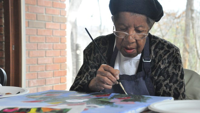 Charity Ray applies the final brush strokes to a still life painting of a flower bouquet.