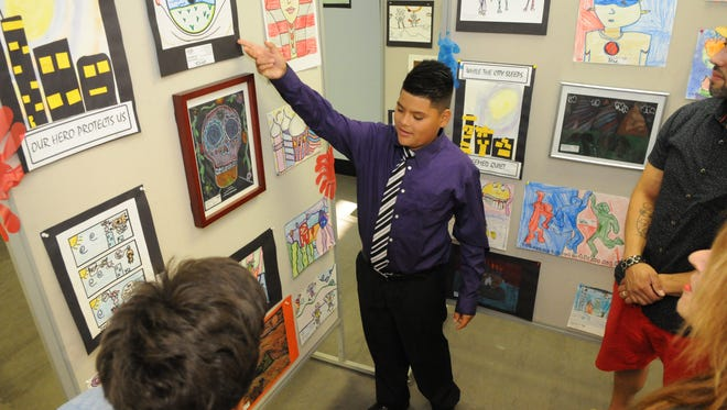 Care Station student Jose Perez, a sixth-grader, discusses his work with teachers and attendees.  The CARE Station, a special needs aftercare program of the Bloomfield Recreation Department, held an Art Exhibit of students' work on June 17, 2016, at the Bloomfield Civic Center.