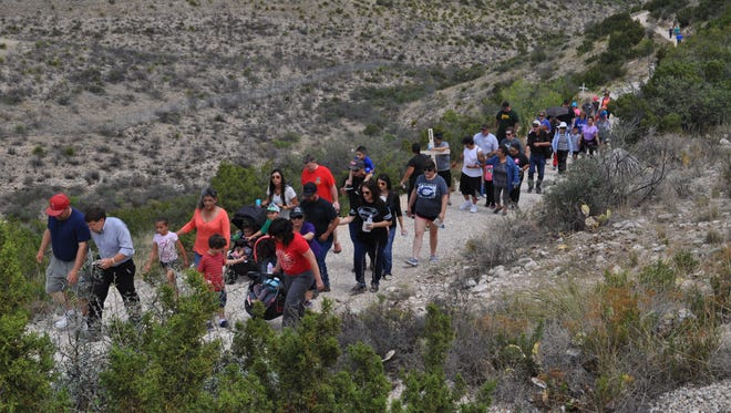 Carlsbad residents walk along Ocotillo Trail on Friday as part of a ceremony to acknowledge the death and resurrection of Jesus Christ. The ceremony was one of four held by St. Edward Catholic Church leading up to Easter Sunday.