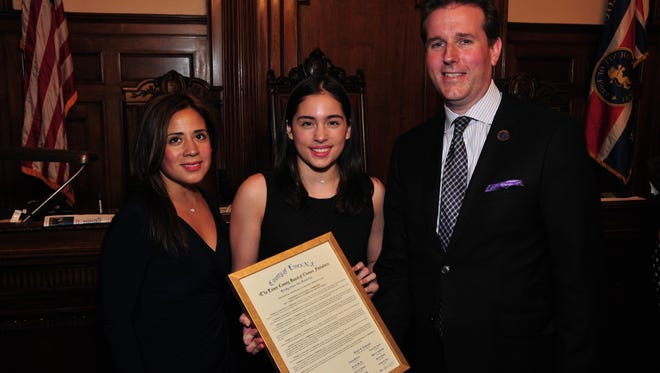 Freeholder Vice President Brendan W. Gill, right, stands alongside honoree Samantha E. Corredor, center, and her mother Giovanna Lopez, as she receives the freeholder board's commendation.