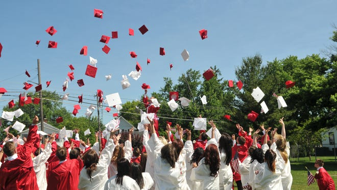 Port Clinton High School graduates toss their caps after receiving their diplomas at True-Lay Stadium.