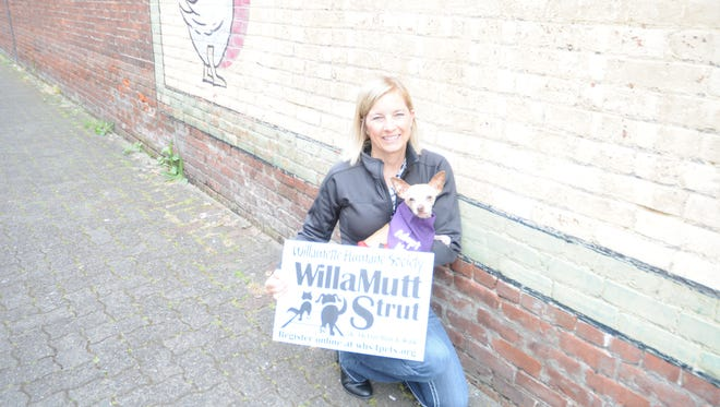 Willamette Humane Society's Krystal Kraig holds Aldo, a 7-year-old Chihauhau mix and a sign touting WillaMutt Strut coming up Sunday.