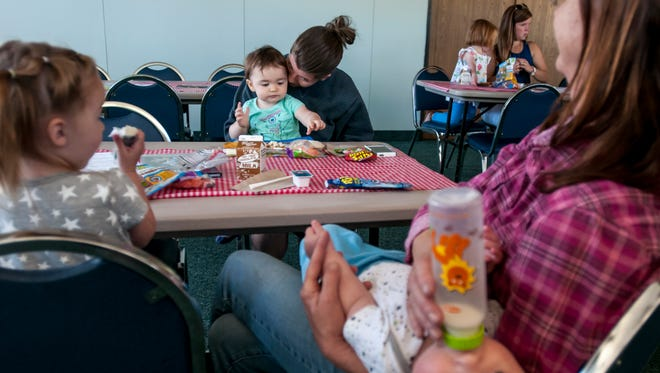 Taisha Mentzer, of Avoca, kisses her daughter, Ava, 1, while sitting with family during Meet Up and Eat Up Wednesday, June 21, 2017 at the St. Clair County Library in Port Huron. The program offers free lunch and breakfast to children under 18 at more than a dozens sites.