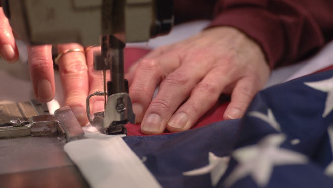 An American flag being sewed together with the stripes and blue field.