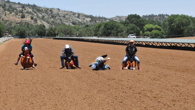 Adults joined the fun during the bouncy-horse race. Chris Zamora, second from right, is a former jockey and current trainer. It appears he gets better results with live racehorses.