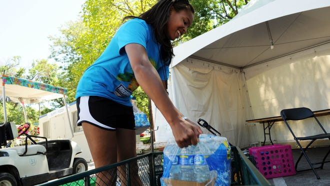 Festival volunteer Danie Remy loads water in to a wagon to take to the Mountain Avenue stage at Bohemian Nights at NewWestFest in 2010. The annual festival is looking for volunteers for this year's 3-day festival.