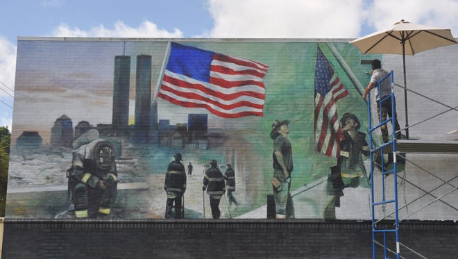 Laurent Dareau paints a mural on the side of the Bonita Springs Fire Station on Old 41 Road.