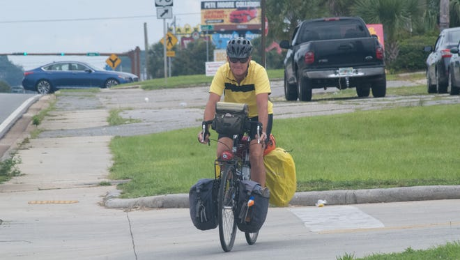 U.S. Army veteran Robert Neidlinger cycles through Pensacola on Tuesday, June 27, 2017, as part of his cross-country bicycle trip to raise awareness about traumatic brain injuries.