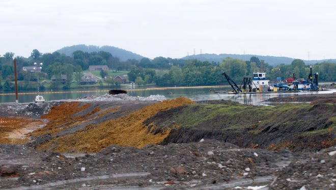 A hydraulic dredge removes coal ash from the Emory River next to the Kingston Fossil Plant. In the foreground, red clay is exposed where the dark gray ash has been completely excavated. Workers are removing 3 million cubic yards of ash sludge from the river in the first phase of the cleanup of the Dec. 22, 2008, spill.