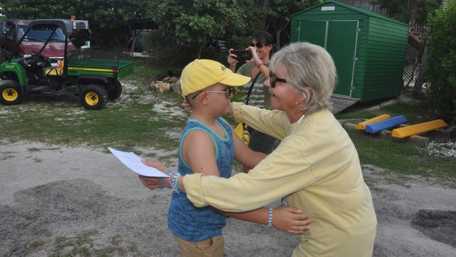 Atticus Chapman, 8, presents Eve Haverfield, founder and president of Turtle Time, with a check for the money he raised.