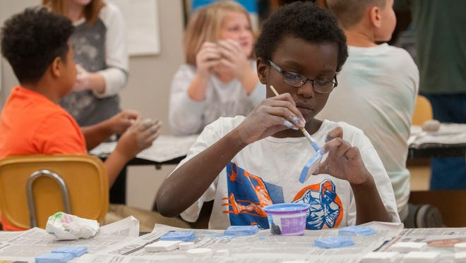 Roosevelt Elementary student Aadam Cooper, 10, paints glaze over ceramic tiles Thursday, Oct. 19 during the Clay and a Concert series in the Fine Arts Building at SC4.