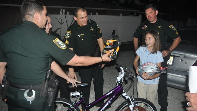 Lee County deputies delivered prizes to young essay contest winners and their families on Dec. 21 in Bonita Springs. The winners were also given a bicycle helmet and a lock for their bicycle. Julia Stolte was excited to be a winner.
