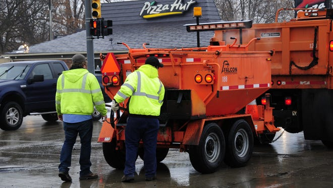 Jason Bobcean and Tom Tramski fill potholes with cold patch in Port Huron in January 2018.