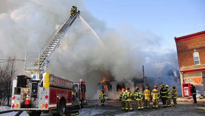 Firefighters pour water on an apartment house fire in Berville. Area fire departments are applying jointly for a grant to buy new radios.