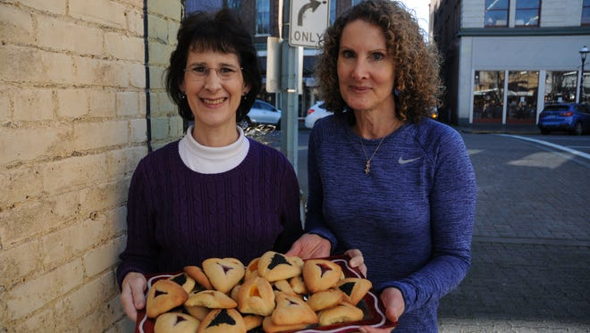 Sherry Dunning, left, and Stacey Brown show off a platter of hamantaschen, a traditional three-sided filled cookie made for Purim, the Jewish festival honoring Queen Esther. The public can order apricot, raspberry or poppy-seed filled cookies.