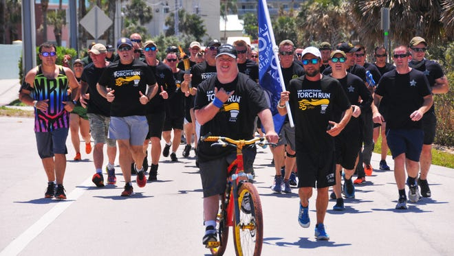 On Thursday afternoon members of the Cocoa Beach Police Department and a city commissioner, led by members of the BCSO Motor Unit, participated in the Law Enforcement Torch Run to raise awareness for Special Olympics. The Cocoa Beach leg of the run was on Ocean Beach Blvd. from the Wakulla Suites to the Cocoa Beach Pier.The Law Enforcement Torch Run is the largest grass-roots fund raiser and public awareness vehicle for Special Olympics. Law enforcement officers from around the country carry the Flame of Hope in honor of the Special Olympic athletes in their areas and around the world. Each year, over 5,000 officers carry the torch on a 1500-mile relay through 67 counties in Florida.