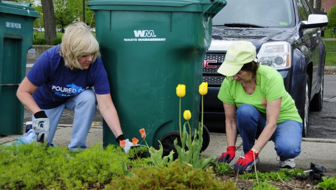 Beth Privette and Diane Horn work in a flower bed at Pine Grove park on Plant Day, May 19, 2018.