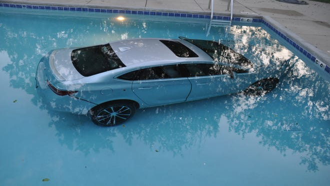 A car sits in the bottom of an apartment complex pool in the 2300 block of Parklawn Drive in Waukesha on Wednesday, May 23. Police say the driver accidentally hit the accelerator when trying to park the vehicle near the pool.