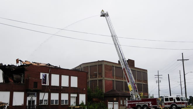 An aerial truck from the Marysville Fire Department pours water on hot spots at the former Chicory Warehouse on 12th Avenue in Port Huron.
