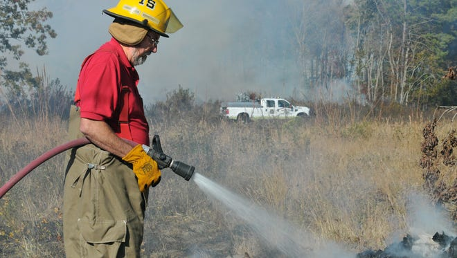 Dave Barry with the Allen Fire Company's Station 15 extinguishes the remnants of a debris pile that caught fire on Flower Hill Church Road in Eden.