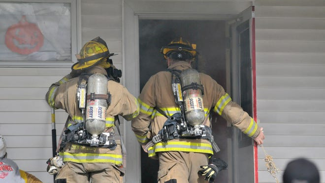 Port Huron fire fighters walk into a home  to block down a fire Thursday, Oct. 30 at 1107 Chestnut Street in Port Huron. There were no injuries in the fire.