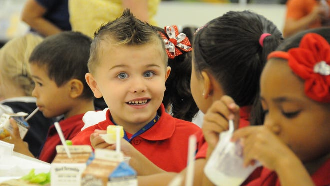 From left to right of the visible children: Isaiah Perez, Brayden Brown, and Alliyah Vinson enjoy fresh fruits and vegetables during lunch at Wood Elementary School in Tempe.