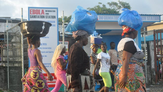 Liberia women walk past a sign warning people of the deadly Ebola virus in Monrovia, Liberia.