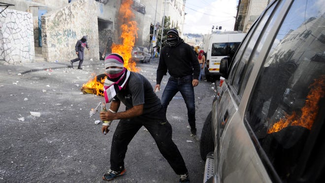 Palestinian youths clash with Israeli border police after Moatez Higazi was shot in east Jerusalem, Thursday.