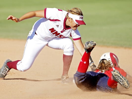 St. John's Yvonne Rericha, right, is tagged out by New Mexico State's Haley Nakamura while trying to steal second base in the fifth inning during an NCAA college softball tournament regional game, Saturday, May 16, 2015, in Tucson, Ariz. (AP Photo/Rick Scuteri)