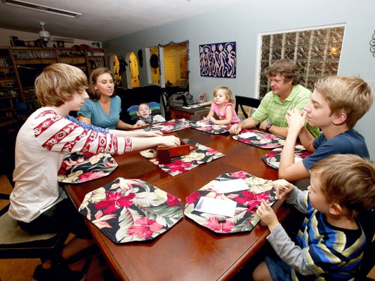 """In this Wednesday, Sept. 30, 2015 photo, from left, Jo Armstrong, Julie Armstrong, Skylar Armstrong, Amelia Anderson, Nathan Anderson, Westley Armstrong and Dean Anderson sit together for a game at their home in Tucson, Ariz. At 42 with a blended family of five, Nathan Anderson runs an acupuncture clinic with his wife, Julie, also an acupuncturist. Combined, their monthly student loans bills approach 1,700. """"More than we spend on groceries and kind of like having a second mortgage,"""" Nathan said. (AP Photo/Rick Scuteri)"""