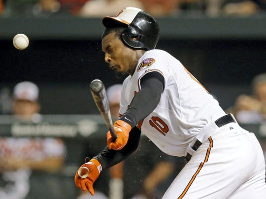 Baltimore Orioles' Adam Jones reacts after a foul ball bounced off his head during an at-bat in the 10th inning of Monday's game against the Atlanta Braves in Baltimore. Baltimore won, 2-1, in 11 innings.