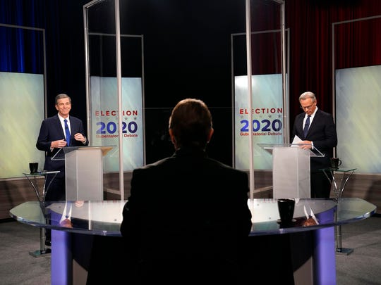 North Carolina Gov. Roy Cooper, left, and Lt. Gov. Dan Forest participate in a live televised debate moderated by Wes Goforth, center, at UNC-TV studios in Research Triangle Park, N.C., on Wednesday.