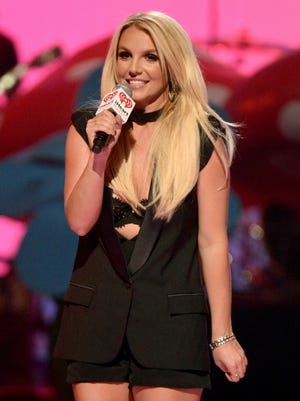 Britney Spears speaks onstage during the iHeartRadio Music Festival at the MGM Grand Garden Arena on Sept. 21, 2013 in Las Vegas. On Oct. 3, 2013, she told a radio host she often feels pressured to be over-the-top risque.