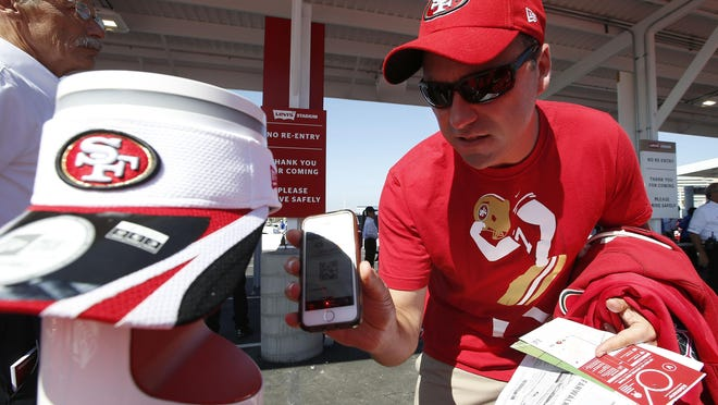 A fan uses a smart phones to scan tickets at Levi's Stadium before an NFL preseason football game in Santa Clara, Calif. Tickets have widely transitioned from paper souvenirs to smartphone screens. These tools are an important piece of the reopening puzzle. They also further test a fan's willingness to potentially sacrifice a little more privacy in an increasingly wired-in world in exchange for the opportunity to sit courtside or behind the plate again.