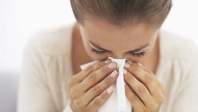 woman blowing nose into handkerchief