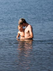 Andrew Harvey plays with his daughter in Lake Superior