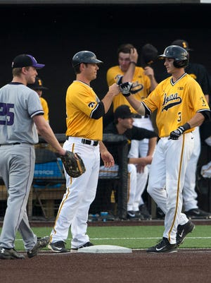 Iowa infielder Nick Roscetti fist-bumps volunteer assistant coach Jeff Clement on April 17 at Duane Banks Field. Clement works with the Hawkeye hitters, catchers and provides scouting reports.