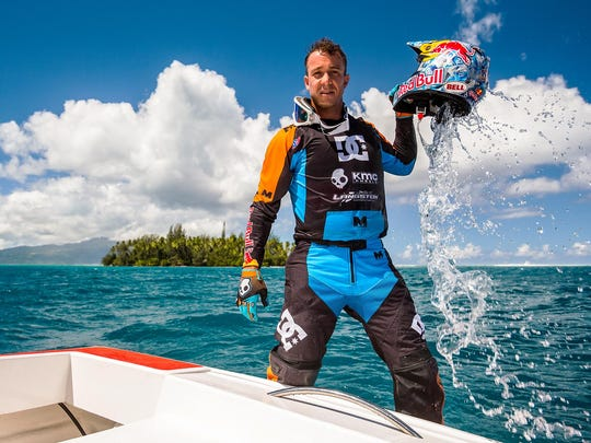 In this April, 2015, photo provided by DC Shoes, daredevil Robbie Maddison poses during a break from his latest stunt, riding his motorcycle across waves in Tahiti, French Polynesia, using ski-like devices on his wheels. (Garth Milan/DC Shoes via AP)
