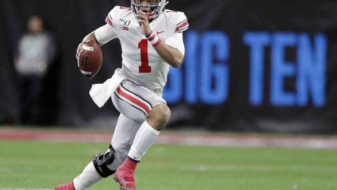 Ohio State quarterback Justin Fields (1) runs with the ball past Wisconsin defensive end Isaiahh Loudermilk during the first half of the Big Ten championship NCAA college football game, Saturday, Dec. 7, 2019, in Indianapolis.