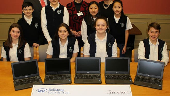 Pictured are Martin F. Connors Jr., president of Rollstone Bank & Trust; Nancy Pierce, principal of St. Leo School; and Melissa Maranda, senior VP of wealth management at RBT, with St. Leo students at the check and laptop presentation.